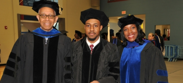 Dr. Jalaal Hayes (center) made DSU history by becoming the youngest-ever doctoral graduate at age 22. Dr. Hayes of Philadelphia was conferred a Ph.D. in Applied Chemistry during the Dec. 20 Commencement. Standing with Dr. Hayes are his advisor Dr. Andrew Goudy, professor of chemistry, and Dr. Cherese Winstead, chair of the DSU Department of Chemistry. (photo via desu.edu) ,